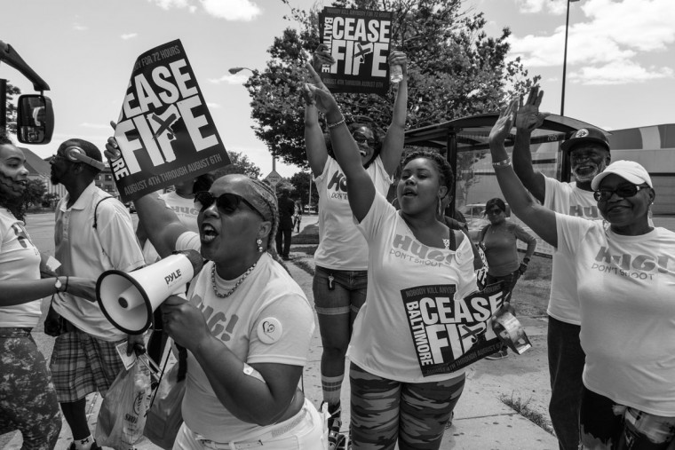 Baltimore, MD -- 8/5/2017 -- Hug Don't Shoot supporters standing on Reisterstown Road waving into the bus passengers . Day 2 of the 72 hours Baltimore Ceasefire. HUG DON'T SHOOT groups march from Druid Hill Park to Pennsylvania Avenue and North Avenue. Supporters gives out countless hugs and water to local Baltimore city residents. (Photo and caption by Paul Lai)