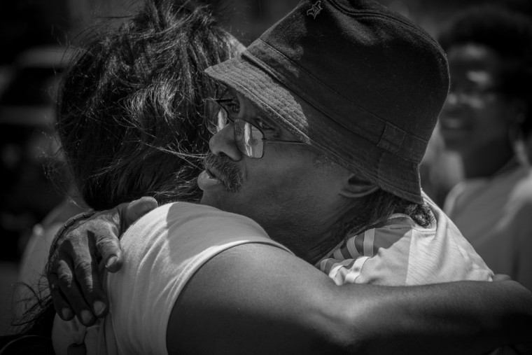 Baltimore, MD -- 8/5/2017 -- A local Baltimore resident receive a hug from one of the march's supporters. Day 2 of the 72 hours Baltimore Ceasefire. HUG DON'T SHOOT groups march from Druid Hill Park to Pennsylvania Avenue and North Avenue. Supporters gives out countless hugs and water to local Baltimore city residents. (Photo and caption by Paul Lai)