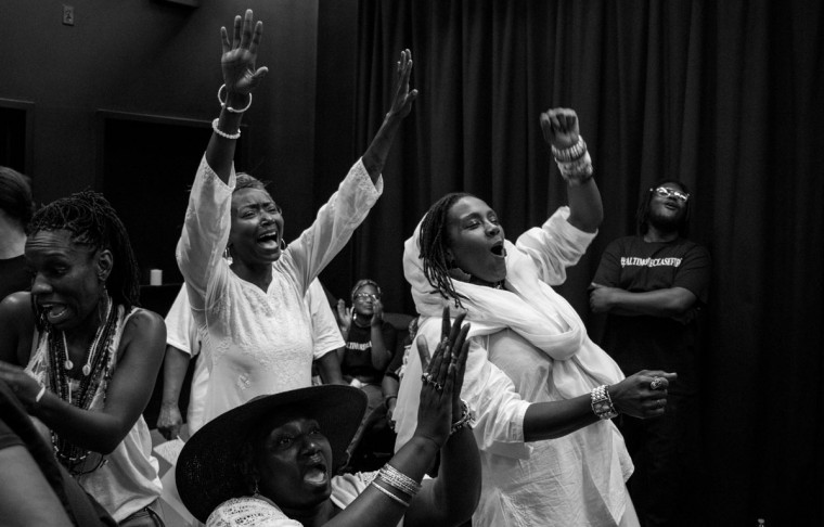 Baltimore, MD -- 8/6/2017 -- Safiyatou (cq) Edwards (center, hands up) and Shameeka Dream (right) react to a speech during a downtown vigil to close out the Baltimore Ceasefire. Day 3 of the 72 hours Baltimore Ceasefire. A downtown vigil gathered over 100 Ceasefire supporters to read the names of 211 victims of violence in Baltimore city. (Photo and caption by Paul Lai)
