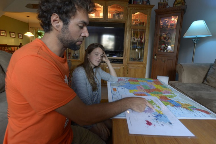 Andres Fluxa and Clemence Egnell point out their itinerary on a world map. After meeting in Colombia, they biked across Europe, Asia and the United States, a journey that has lasted two years. (Christina Tkacik/Baltimore Sun)