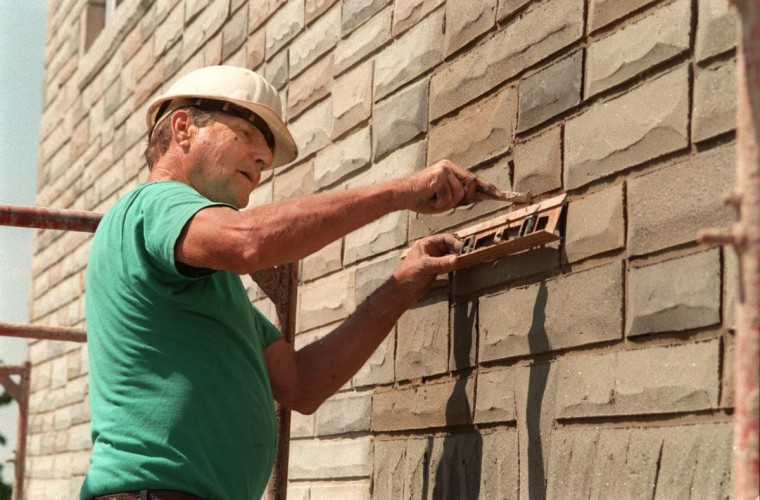 "Aado Vaigro, an Estonian-born craftsman who puts formstone on houses for his company, Modern Stone, working on a corner attached home in North Point Village. He has been doing formstone since 1950, but in recent years the trend has been more toward removing the fake stone covering. Vaigro uses level as straight edge to carve lines imitating mortar between ""stone"" blocks. (Amy Davis/Baltimore Sun archives)"