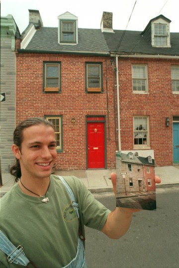 A renovated alley home at 71 S. Bethel St., built in the 1790's. He is holding a before picture, showing the Formstone exterior he removed. (Amy Davis/Baltimore Sun)