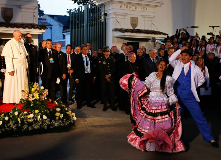 Pope Francis looks at a couple performing a traditional dance outside the Nunciature in Bogota. AFP PHOTO / John Vizcaino