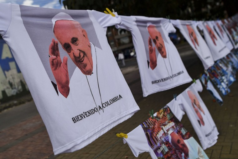 T-shirts commemorating the visit of Pope Francis to Colombia, are sold at a stand set up along the route to be taken by the pontiff upon his arrival in Bogota. AFP PHOTO / Luis ROBAYO