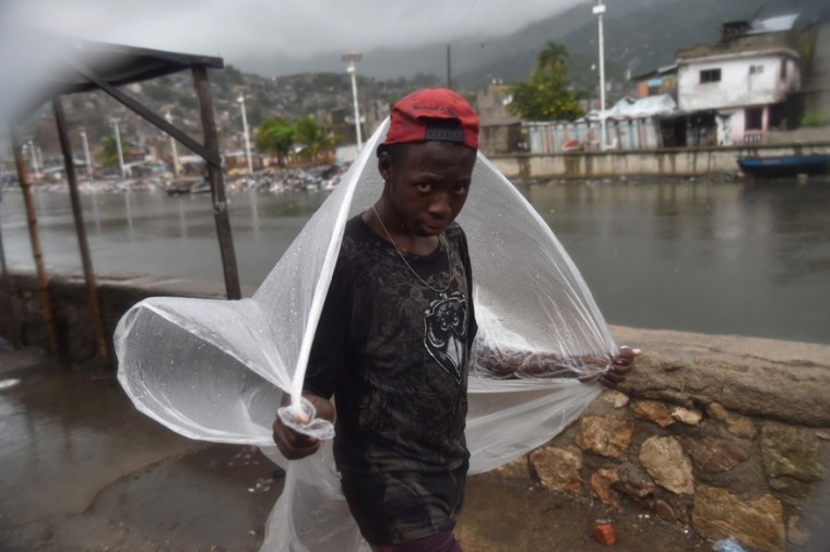 A boy takes cover from the rain in the Shada neighborhood, in Cap-Haitien on September 7, 2017, as Hurricane Irma approaches. (HECTOR RETAMAL/AFP/Getty Images)