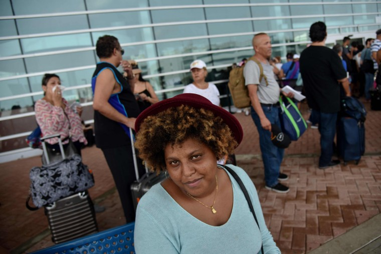 Rose Marie Garcia sits at Luis Munoz Marin International Airport, in San Juan, Puerto Rico, on September 26, 2017, having had a flight for today, the airline resceduled for October 8, 2017 The US island territory, working without electricity, is struggling to dig out and clean up from its disastrous brush with the hurricane, blamed for at least 33 deaths across the Caribbean. (AFP PHOTO / HECTOR RETAMAL)