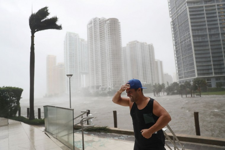 A person battles high winds and rain after taking pictures of the flooding along the Miami River as Hurricane Irma passes through on September 10, 2017 in Miami, Florida. Hurricane Irma made landfall in the Florida Keys as a Category 4 storm on Sunday, lashing the state with 130 mph winds as it moves up the coast. (Photo by Joe Raedle/Getty Images)