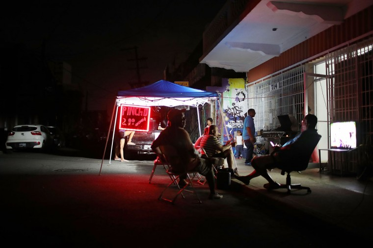 SAN JUAN, PUERTO RICO - SEPTEMBER 23: People hang out near a business that is using a generator to keep its lights on as they wait for the damaged electrical grid to be fixed after Hurricane Maria passed through the area on September 23, 2017 in San Juan, Puerto Rico. Puerto Rico experienced widespread damage after Hurricane Maria, a category 4 hurricane, passed through. (Photo by Joe Raedle/Getty Images)