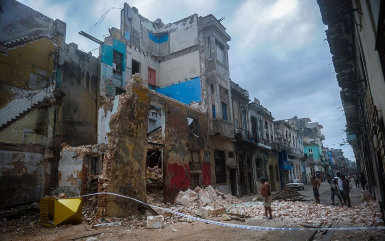 Cubans stand by a collapsed building in Havana, on September 9, 2017. Irma's blast through the Cuban coastline weakened the storm to a Category Three, but it is still packing 125 mile-an-hour winds (205 kilometer per hour) and was expected to regain power before hitting the Florida Keys early Sunday, US forecasters said. The Cuban government extended its maximum state of alert to three additional provinces, including Havana, amid fears of flooding in low-lying areas. (Yamil Lagey/AFP/Getty Images)
