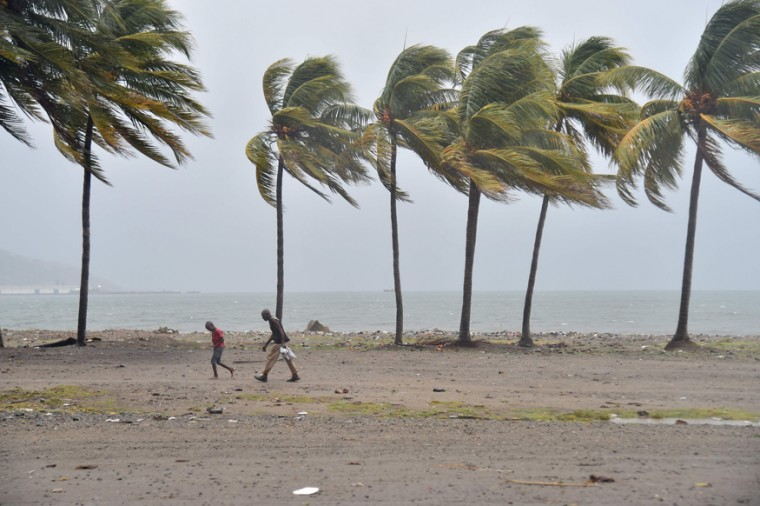 Haitian people walk through the wind and rain on a beach, in Cap-Haitien on September 7, 2017, as Hurricane Irma approaches. (HECTOR RETAMAL/AFP/Getty Images)