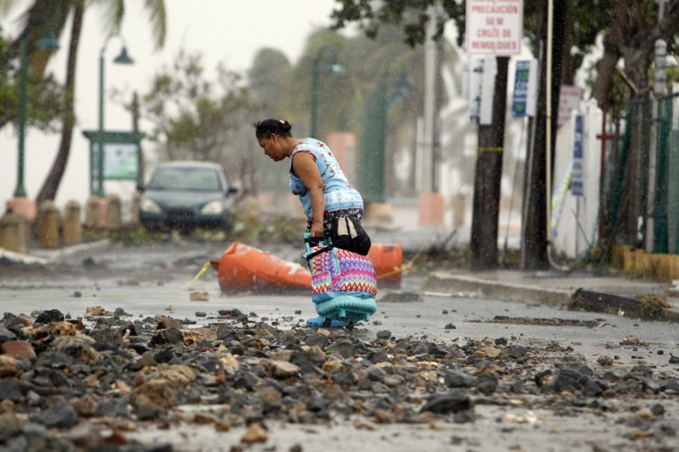 A woman pulls a travel case on a rock-scattered road in the aftermath of Hurricane Irma in Fajardo, Puerto Rico, on Sept. 7, 2017. (RICARDO ARDUENGO/AFP/Getty Images)