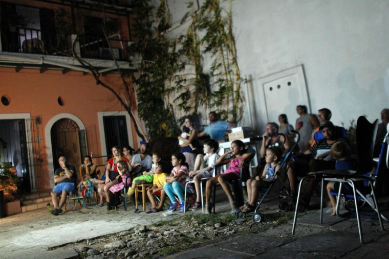 A group of people watch a movie at an makeshift outdoor theatre at night in Old San Juan, Puerto Rico, on September 25, 2017, where a 7pm-6am curfew has been imposed following impact of Hurricane Maria on the island. (AFP PHOTO / Ricardo ARDUENGO)