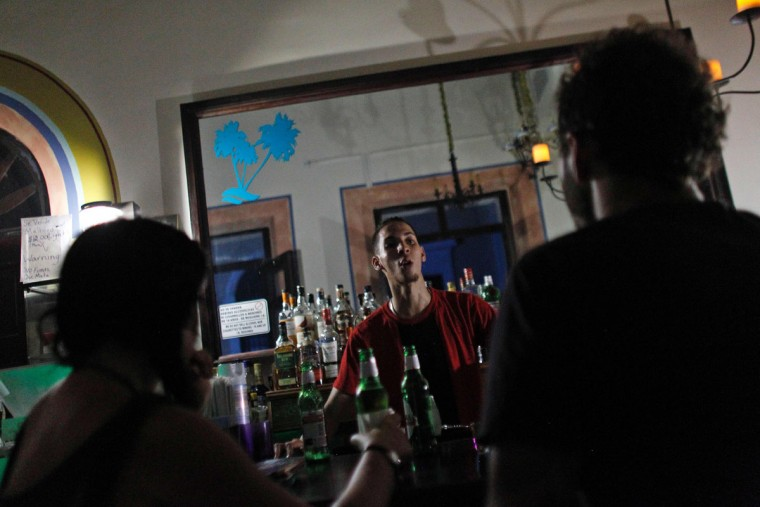 A bartender talks to a couple at a candle-lit bar at night in Old San Juan, September 25, 2017, where a 7pm-6am curfew has been imposed following the impact of Hurricane Maria on the island. (AFP PHOTO / Ricardo ARDUENGO)