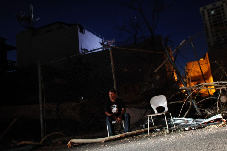A man sits on a chair beside a road at night September 25, 2017 in San Juan, Puerto Rico, where a 7pm-6am curfew has been imposed following the impact of Hurricane Maria on the island. (AFP PHOTO / Ricardo ARDUENGO)