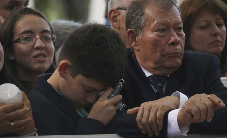 A boy prays with a cross in his hand as he waits for Pope Francis. (AP Photo/Ivan Valencia)