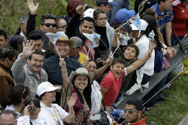People cheer as they wait for Pope Francis to pass along the road between the airport and the Nunciatura in Bogota, Colombia. (AP Photo/Fernando Vergara)