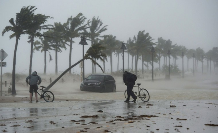 Two men walk their bicycle along a flooded street on the waterfront of Fort Lauderdale, Fla., as Hurricane Irma passes through on Sunday, Sept. 10, 2017. (Paul Chiasson/The Canadian Press via AP)