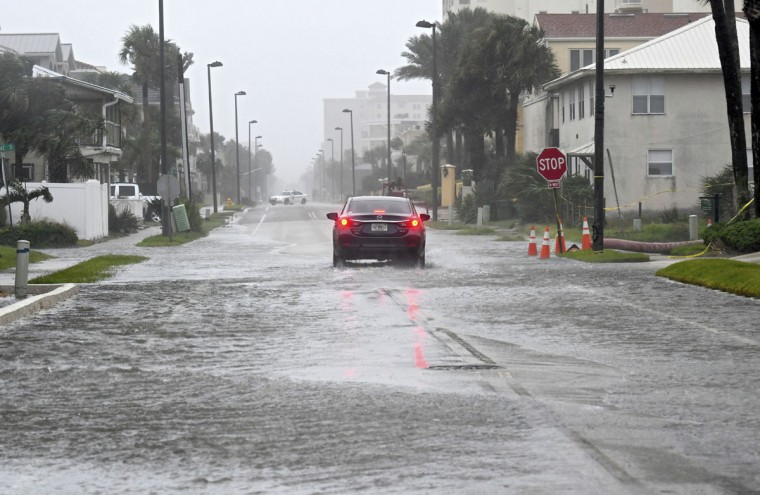 A car makes its way up a flooded 1st Street South in Jacksonville Beach, Fla., Sunday, Sept. 10, 2017. The direct effects of Irma will hit the area late Sunday night or Monday morning. (Bob Mack/The Florida Times-Union via AP)