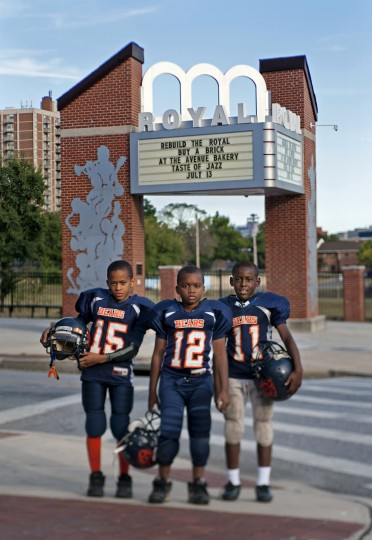 "Royal -1329 Pennsylvania Avenue --  From left, Tyler Saunders, Traveis Howell and Jawuan Maultsby were ready for football practice in 2013 on the field that replaced the Royal and other businesses. The Royal, much beloved in the African-American community for its superb live entertainment, was torn down in 1971.  From ""Flickering Treasures: Rediscovering Baltimore's Forgotten Movie Theaters,"" © Amy Davis."