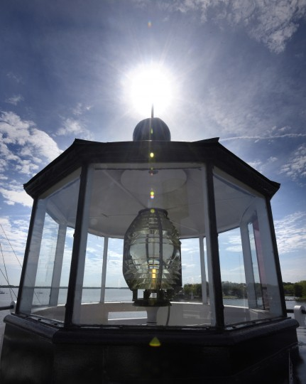 The fresnel lens in the Lantern Room shines on the Miles River at Navy Point. The lens' multifaceted glass prisms focus the rays of light into a single beam making it more effective compared to other lights. (Algerina Perna/Baltimore Sun)