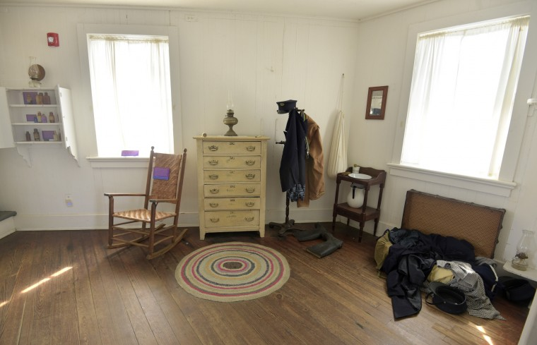 Pictured is the living and office space in the lighthouse. Clothes on the stand and in the trunk are those which would have been worn by the keeper. The medicine in the wall cabinet served the keeper's medical needs while they were on duty for 25 days straight. (Algerina Perna/Baltimore Sun)