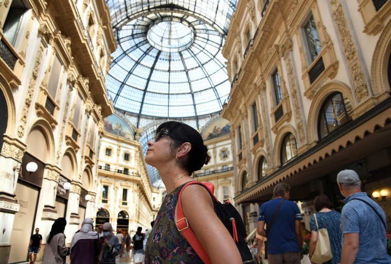 Milan, Italy -- Loretta Perna poses for a photograph in Galleria Vittorio Emanuele II while admiring the architecture of the shopping center topped with a glass and iron ceiling. (Algerina Perna/Baltimore Sun)