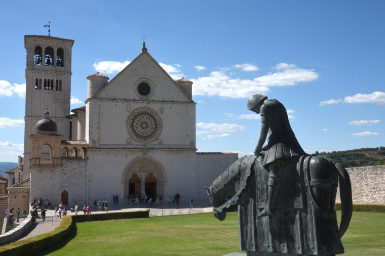 Assisi,Italy -- The metal sculpture at right depicts Saint Francis of Assisi in 1204 returning from battle between Perugia and Assisi. The Basilica of Saint Francis of Assisi in the background was built in his honor for his good works and for founding the Franciscan order in 1181.  Born John di Bernardone,his father changed his son's name to Francisco. After a life of frivolity and extravagance, he went to war. After experiencing visions of Jesus Christ, he completely altered his lifestyle. He died in 1224. (Algerina Perna/Baltimore Sun)