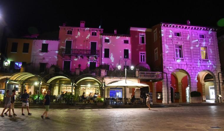 Desenzano del Garda, Italy -- Colorful lights dance on buildings in the town's main piazza. (Algerina Perna/Baltimore Sun)