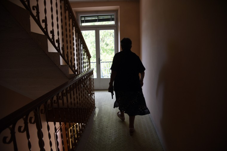 Trento, Italy --  Lina, the current owner of the apartment complex which my mother's family owned in the 1930's, walks down a darkened hallway. My mother's father died there in 1934. (Algerina Perna/Baltimore Sun)