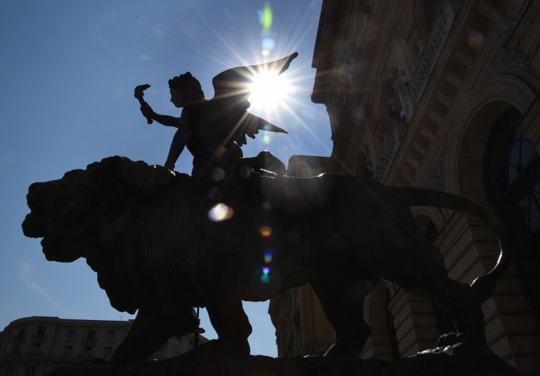 Napes, Italy -- Throughout Italy in towns large and small, sculptures adorn buildings and piazzas. A winged boy carrying a torch perched upon a lion guards one side of the entrance to the Camera Di Commercio building on Via W. Aspreno. Algerina Perna
