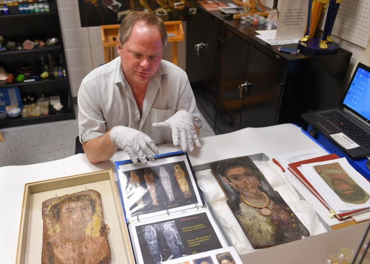 Glenn Gates is a Conservation Scientist at the Walters Art Museum and is pictured by mummy portraits made on Beechwood and LInden wood that date to 130-300 AD.     (Lloyd Fox/Baltimore Sun)