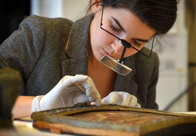 Amaris Sturm, an intern in the objects conservation lab at the Walters Art Museum, carefully cleans and stabilizes a 16th century frame and painting, focusing on the detailed enamel on the frame.    (Lloyd Fox/Baltimore Sun)