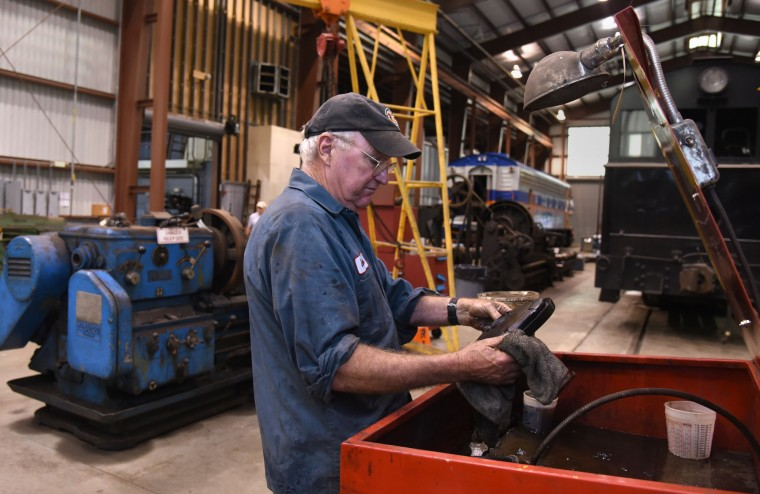 Denny Marron, a long-time volunteer, cleans a train's brake cylinder cup in the B & O Railroad museum's restoration shop in west Baltimore.  (Barbara Haddock Taylor/Baltimore Sun)