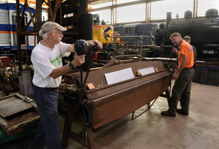 Volunteer Roger Frye, left, and master carpenter Jamie Partridge, right, use a turn of the century bending brake to bend light sheet metal  at the B & O Railroad museum's restoration shop in west Baltimore.  (Barbara Haddock Taylor/Baltimore Sun)