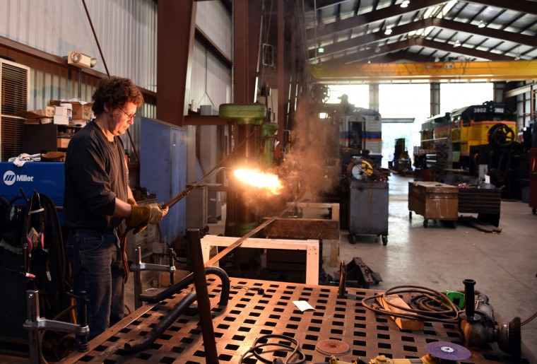 George Harwood, master metal conservator and restorationist for 27 years at the B & O Railroad museum's restoration shop in west Baltimore, uses an acetylene torch to make metal strips for a locomotive's side panels.   (Barbara Haddock Taylor/Baltimore Sun)