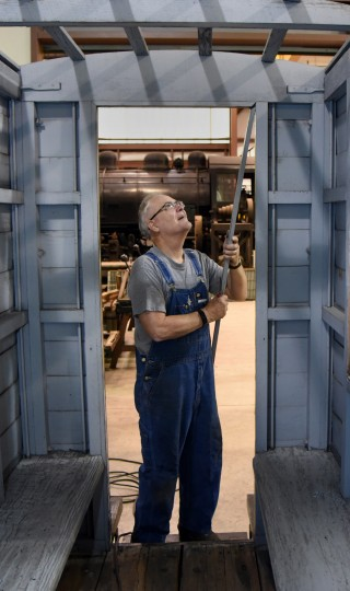 "Leon Crookshank of Glen Burnie, works on the door frame opening on the ""Pioneer,"" a reproduction of a horse-drawn railroad car, at the B & O Railroad museum's restoration shop in west Baltimore.  (Barbara Haddock Taylor/Baltimore Sun)"