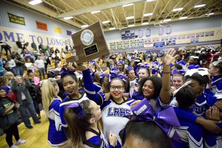 Long Reach's Jordyn Tyler holds the team trophy while she and her team celebrate winning the Howard County Cheerleading Championships at Long Reach High School in Columbia.