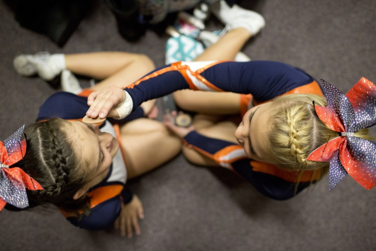 Reservoir cheerleaders Rosette Rand, left, and Natalie Shope, right, 14, prepare for the start of the Howard County Cheerleading Championships at Long Reach High School in Columbia.