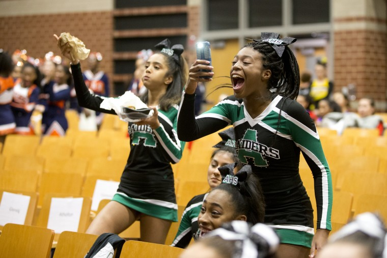 "Atholton's Morgan Nasir, 18, cheers while she takes video of the cheer battle before the start of the Howard County Cheerleading Championships at Long Reach High School in Columbia.  Nasir said, ""I live for cheers like this""."