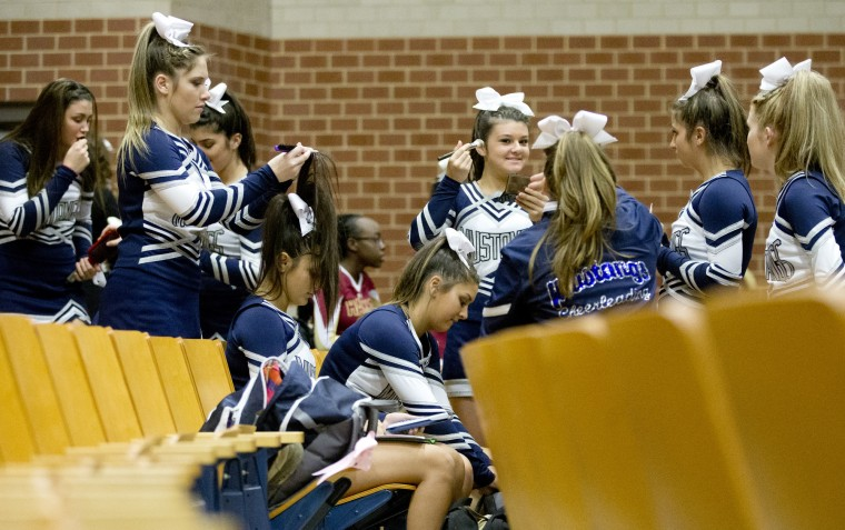 Marriotts Ridge cheerleaders Emma Parks, left, 17, does her teammate Lilly Vazquez's, 17, hair while she does homework before the start of the Howard County Cheerleading Championships at Long Reach High School in Columbia.