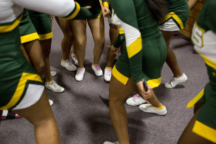 Wilde Lake cheerleaders start a dance circle before the start of the Howard County Cheerleading Championships at Long Reach High School in Columbia.