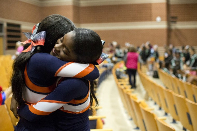 Reservoir cheerleaders Taylor Williams, left, 16, and teammate Jola Bamisaiye, right, 16, embrace before the start of the Howard County Cheerleading Championships at Long Reach High School in Columbia.