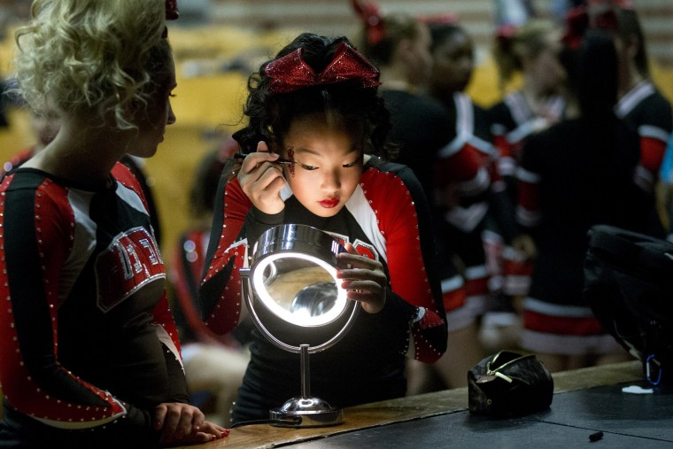 Glenelg cheerleader Allie Gorsuch, 15, puts on makeup before the start of the Howard County Cheerleading Championships at Long Reach High School in Columbia.