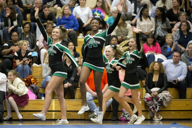 Atholton cheerleaders come out to compete during the Howard County Cheerleading Championships at Long Reach High School in Columbia.