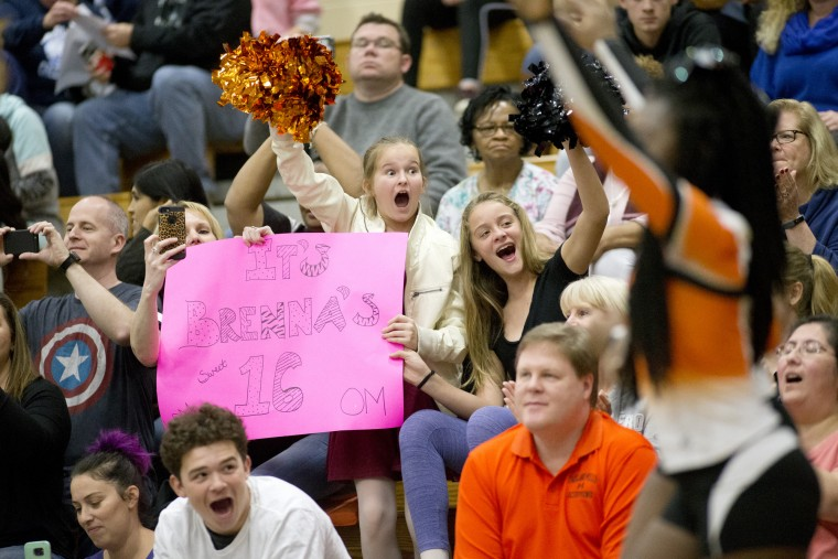 Oakland Mills' fans Katie Baus, her daughter Cara Baus, center, 12, and friend Abby McDonough, right, cheer as the team enters the gym during the Howard County Cheerleading Championships at Long Reach High School in Columbia.