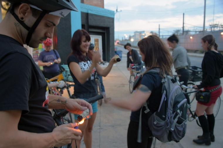 "Manny Ruiz of Union Square lights his smudging stick along with others at Baltimore Bicycle Works before riding to City Hall and Wyman Park to participate in ""smudging,"" on a bike run recognizing the second Baltimore Cease Fire weekend. (Karl Merton Ferron / Baltimore Sun Staff)"