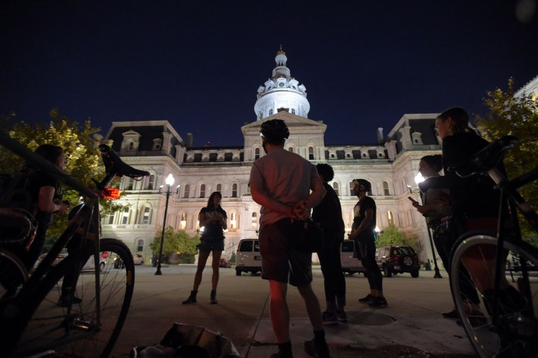 Bicyclists speak about their efforts of smudging during a stop at Baltimore's City Hall, on a bike run recognizing the second Baltimore Cease Fire weekend. (Karl Merton Ferron / Baltimore Sun Staff)