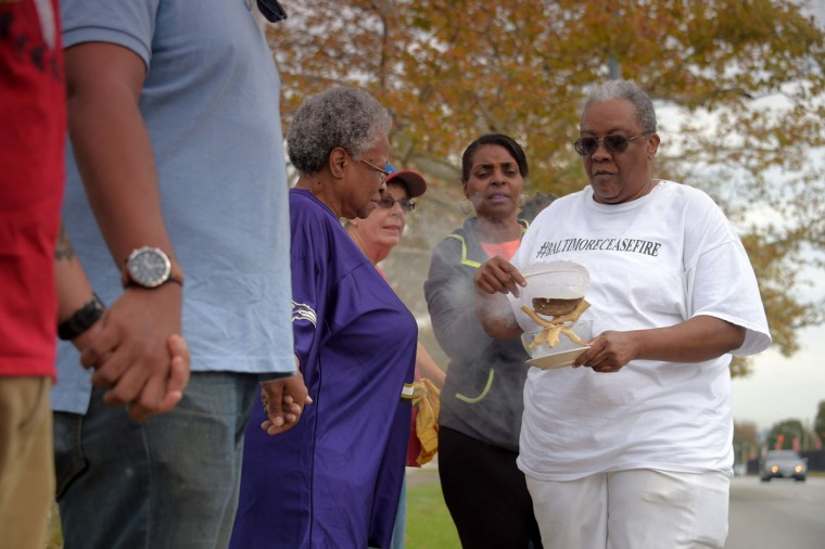 Community activist Valerie Keys, burns sage incense which she claims, cleanses the energy wherever people are, as Darlene Cain, with Mothers on the Move, Inc.,follows to keep the vessel filled as people hold hands during the second Baltimore Cease Fire weekend, held at Edmondson Village Shopping Center. (Karl Merton Ferron / Baltimore Sun Staff)