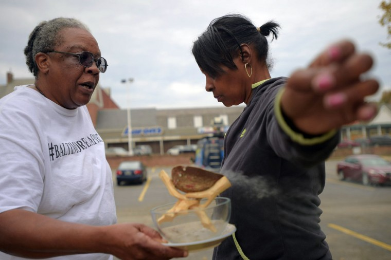 Community activist Valerie Keys, burns sage incense which she claims, cleanses the energy wherever people are, as Darlene Cain, with Mothers on the Move, Inc., holds out her arms during the second Baltimore Cease Fire weekend, held at Edmondson Village Shopping Center. (Karl Merton Ferron / Baltimore Sun Staff)