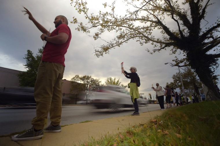 Miguel Carmona of Baltimore (left) and Mary Buchanan of Catonsville, who attends church in the neighborhood, hold up placards for passing motorists during the second Baltimore Cease Fire weekend, held at Edmondson Village Shopping Center. (Karl Merton Ferron / Baltimore Sun Staff)